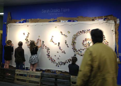 """Prayers for a Transformation"" visitors pinning butterflies at the MOSH."